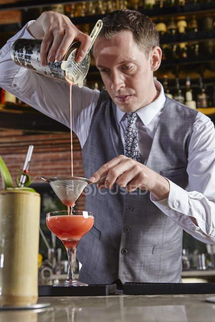 Кавказький Бармен заливки коктейль в барі — стокове фото