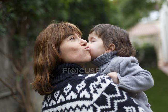 Мати і дочка цілуватися на щоці — стокове фото