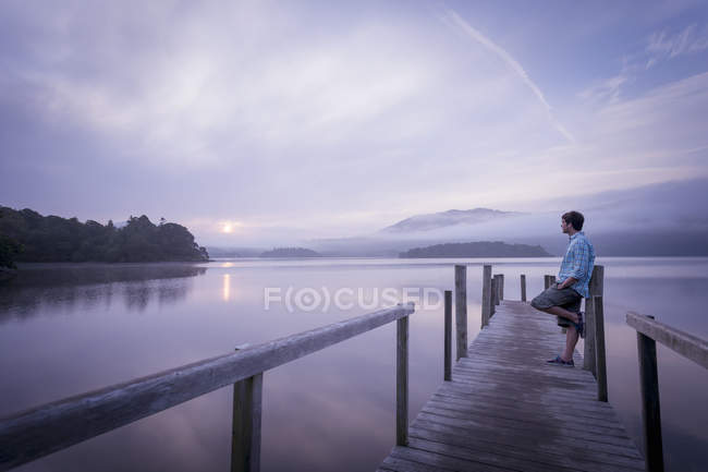 Man on pier by tranquil lake, Cumbria, England, UK — Stock Photo