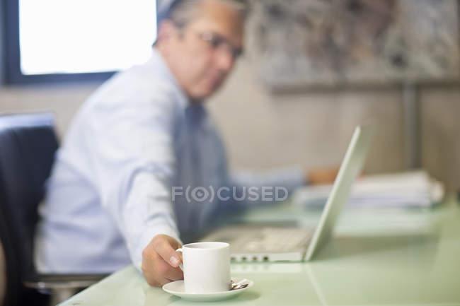Uomo d'affari maturo prendendo una pausa caffè in ufficio — Foto stock