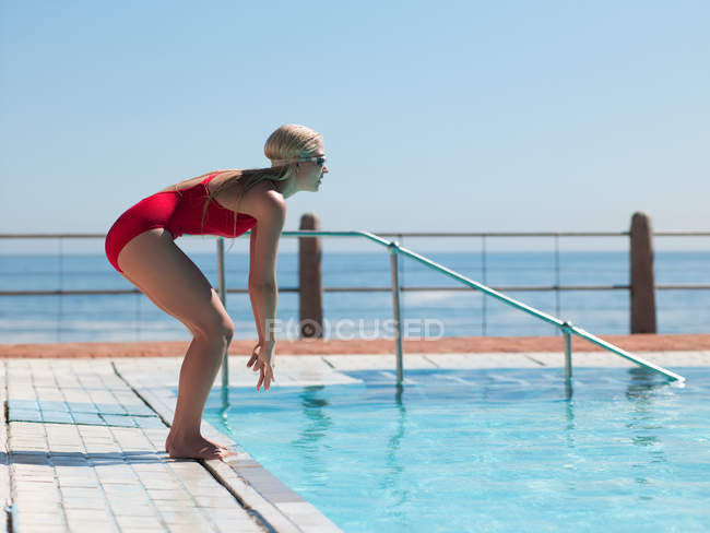 Young woman diving into swimming pool — Stock Photo