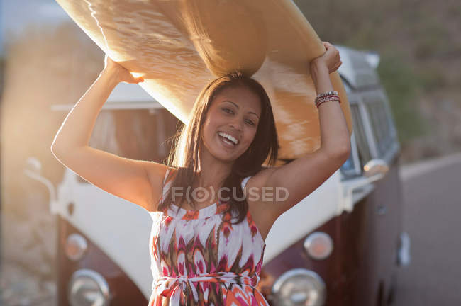 Young woman holding surfboard on road trip, smiling — Stock Photo