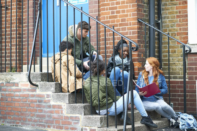 Young adult college students chatting and revising on campus stairs — Stock Photo