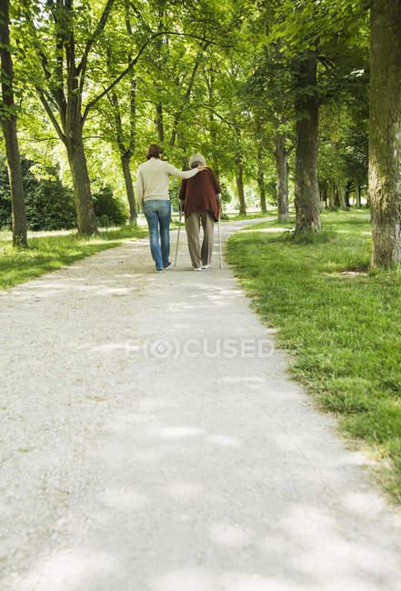 Старша жінка і внучка Прогулюючись парком, використовуючи паличку для прогулянок — стокове фото