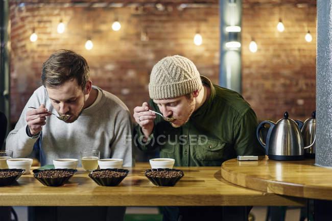 Команда кофейни дегустирует чашки кофе и кофейные зерна — стоковое фото