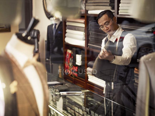 Tailor looking at fabric in traditional tailors shop — Stock Photo