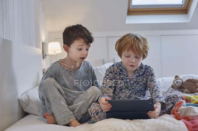Garçons en pyjama utilisant une tablette numérique au lit — Photo de stock