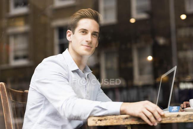 Vista finestra di giovane uomo d'affari con computer portatile in caffè — Foto stock