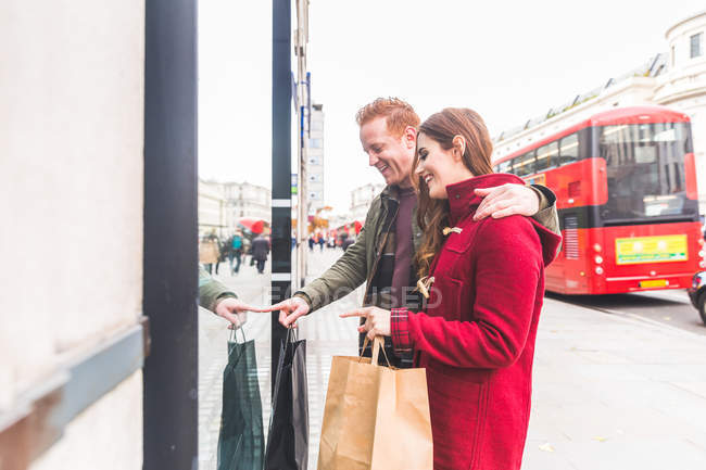 Couple window-shopping outdoors, London, UK — Stock Photo