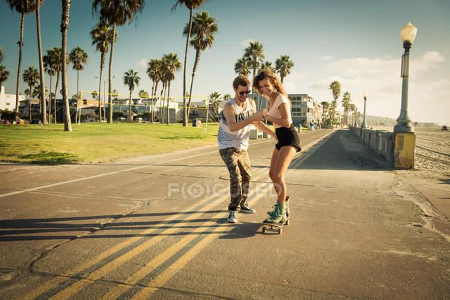 Молодая женщина на скейте в Сан-Диего пляж, помогая бойфренд — стоковое фото