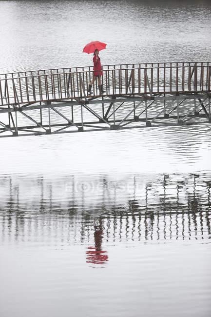 Young woman in red crossing footbridge in rain — Stock Photo