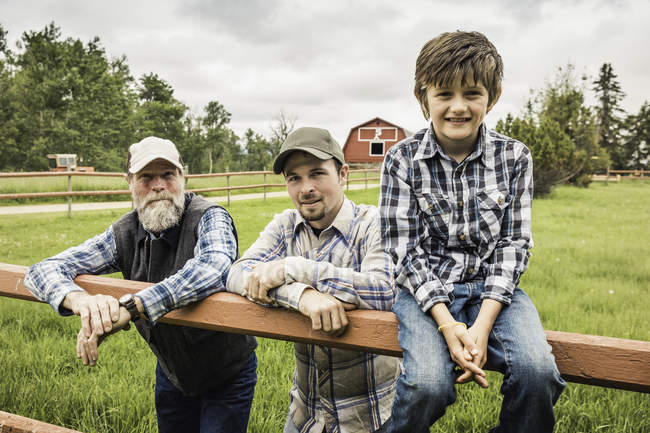 Multi generation family by fence on farm looking at camera smiling — Stock Photo