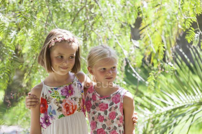 Откровенный портрет двух девушек, смотрящих в сад — стоковое фото
