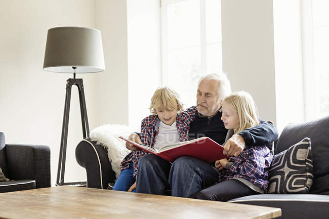 Grandfather reading book to grandchildren — Stock Photo