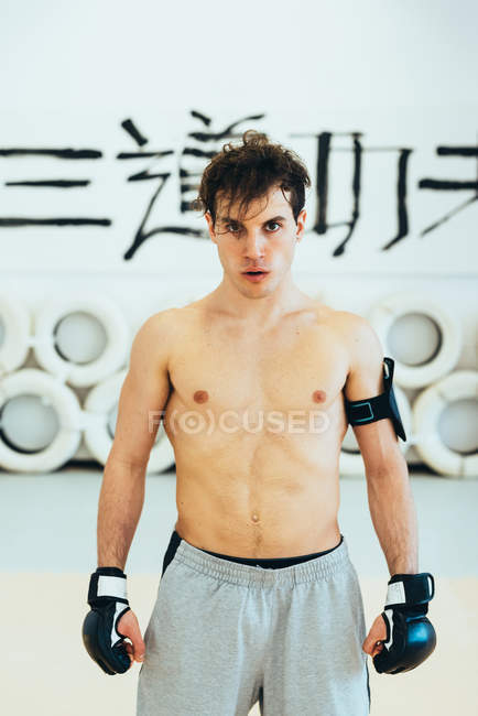Man in gym wearing kickboxing gloves and heart rate monitor looking at camera — Stock Photo