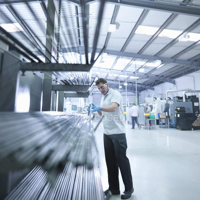 Engineer inspecting steel rods in factory — Stock Photo