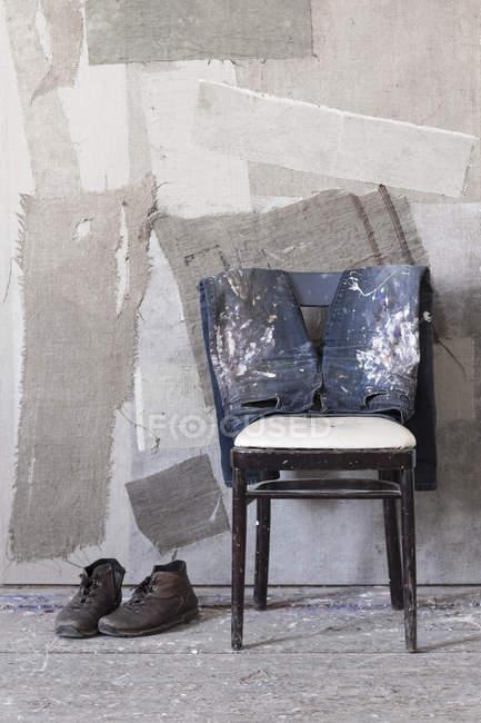 Par de botas, vaqueros sucios en silla delante de la pared pintada - foto de stock