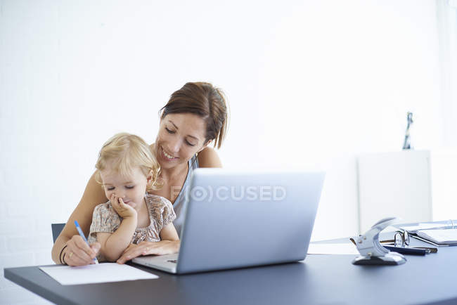 Mid adult woman writing notes with toddler daughter on her lap — Stock Photo