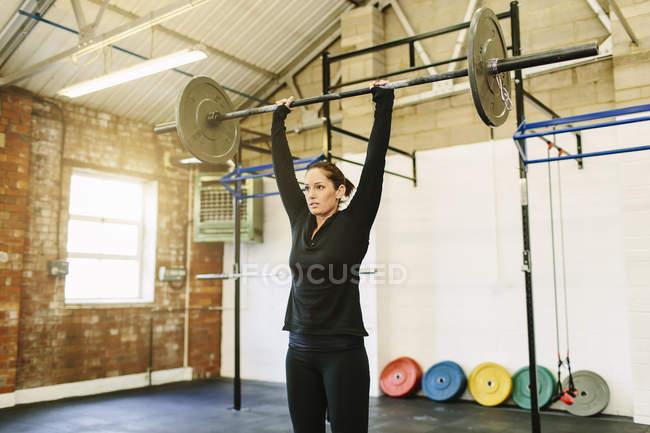 Frau heben Langhantel im Fitness-Studio — Stockfoto