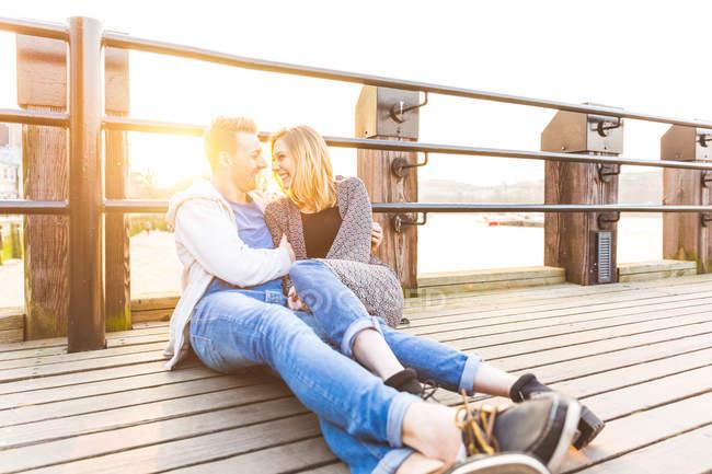 Молодая пара прислонилась к перилам обнимаясь, лицом к лицу улыбаясь — стоковое фото