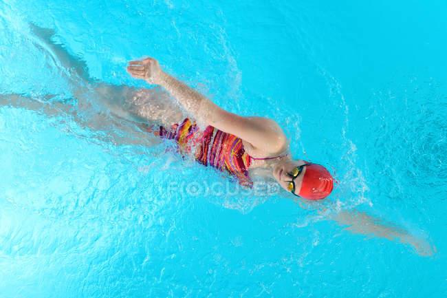 Teenage girl doing front crawl in swimming pool — Stock Photo