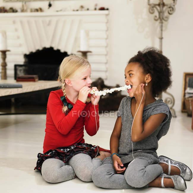 Girls eating popcorn off string — Stock Photo