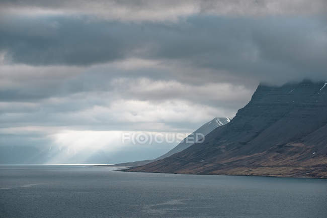 Coastline mountains and dramatic cloudy sky with sunbeams — Stock Photo
