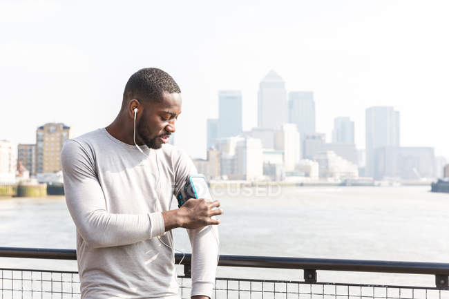 Юнак на відкритому повітрі, використовуючи діяльності tracker, носити навушники — стокове фото