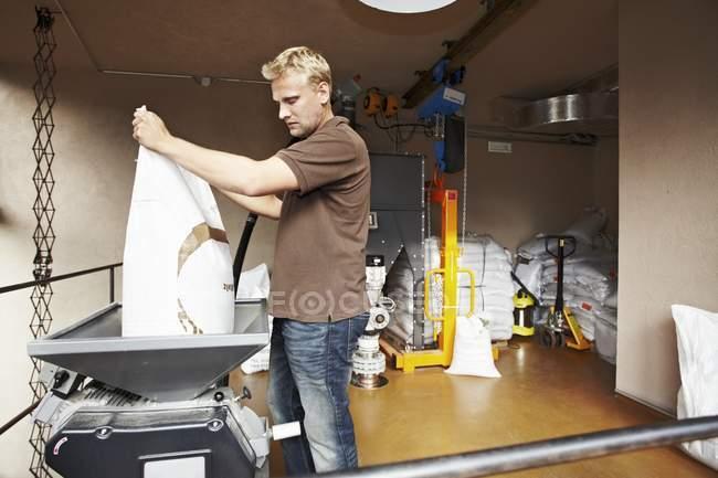 Uomo vagliando grani su squame di peso nel birrificio — Foto stock