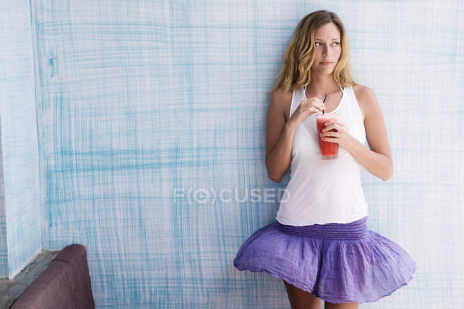 Girl standing up against blue wall with red smoothie in her hands — Stock Photo