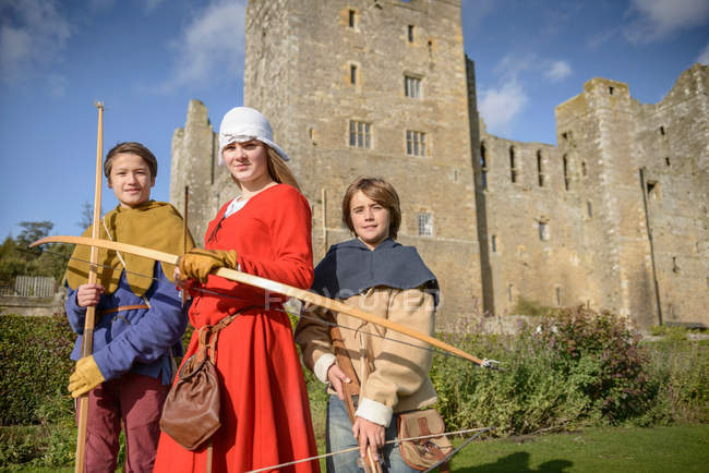 Portrait of history students in period dress with longbows and crossbow outside Bolton Castle, a 14th century Grade 1 listed building, Scheduled Ancient Monument — Stock Photo