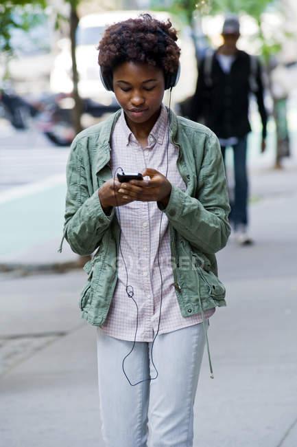 Портрет молодой женщины в наушниках, идущей по улице — стоковое фото