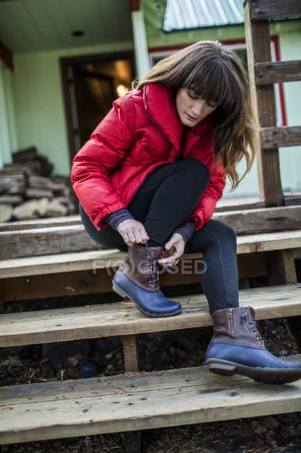 Молода жінка сидить на кроці, зав'язуючи шнурки чобота — стокове фото