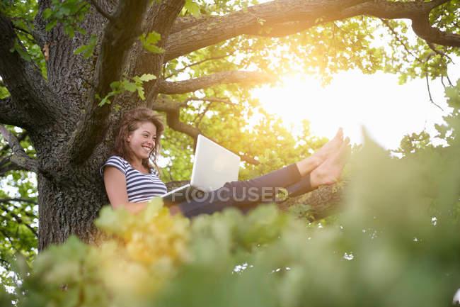 Улыбающаяся женщина с ноутбука на дереве — стоковое фото