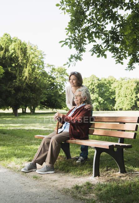 Старша жінка, сидячи на лавці в парку в парку з внучкою — стокове фото