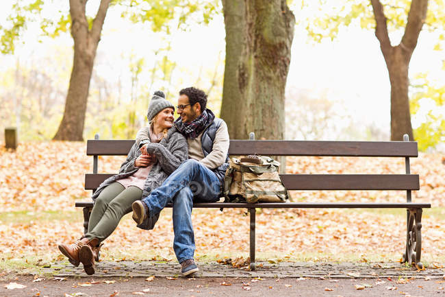 Smiling couple sitting on park bench — Stock Photo