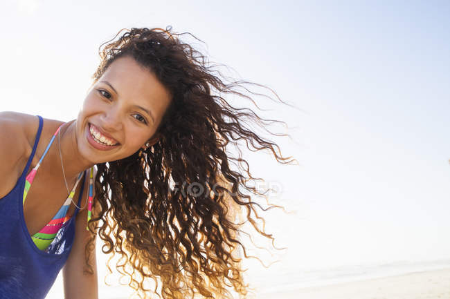 Portrait of curly haired woman looking at camera smiling — Stock Photo