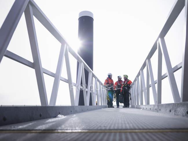Ingenieros de parques eólicos marinos en el puerto en la pasarela - foto de stock
