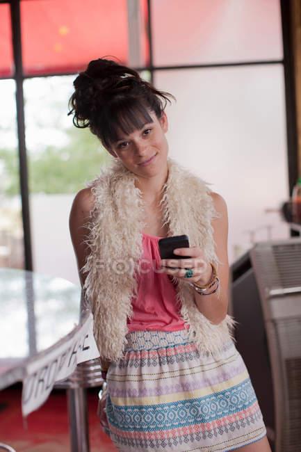 Mujer joven sosteniendo el teléfono móvil en el comedor, retrato - foto de stock