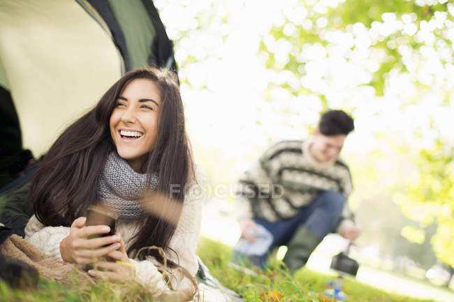 Jovem na tenda usando smartphone, rindo — Fotografia de Stock