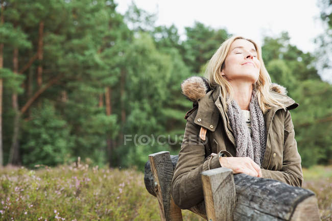 Mid adult woman on bench with eyes closed — Stock Photo