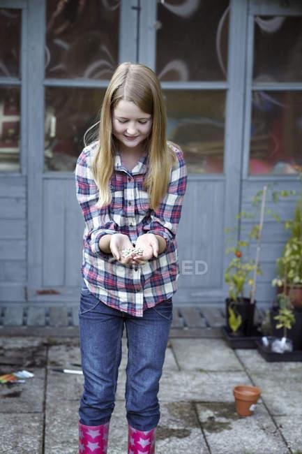 Girl in garden cupping seeds in hands — Stock Photo
