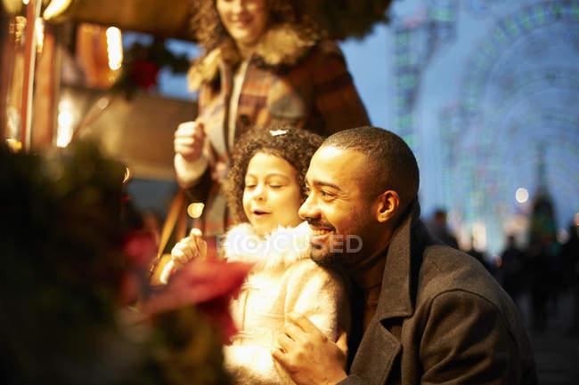Jeune famille à la fête foraine dans la nuit, s'amuser — Photo de stock