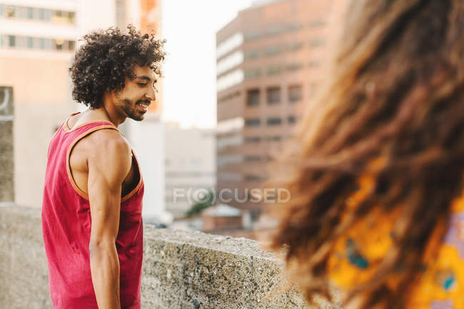Jovem olhando para o lado da namorada no telhado do arranha-céu — Fotografia de Stock