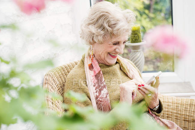 Senior woman using mobile phone in garden — Stock Photo