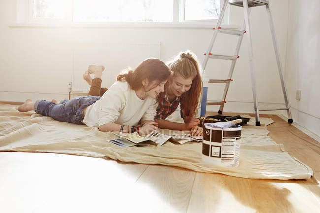 Two teenage sisters lying on floor looking at colors swatches — Stock Photo