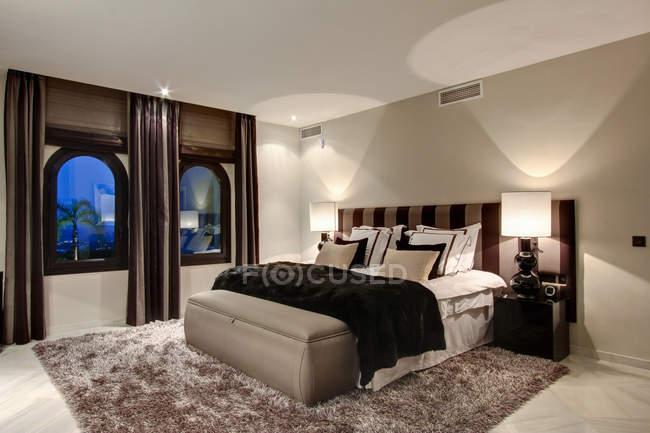 Cama e janelas no quarto moderno — Fotografia de Stock