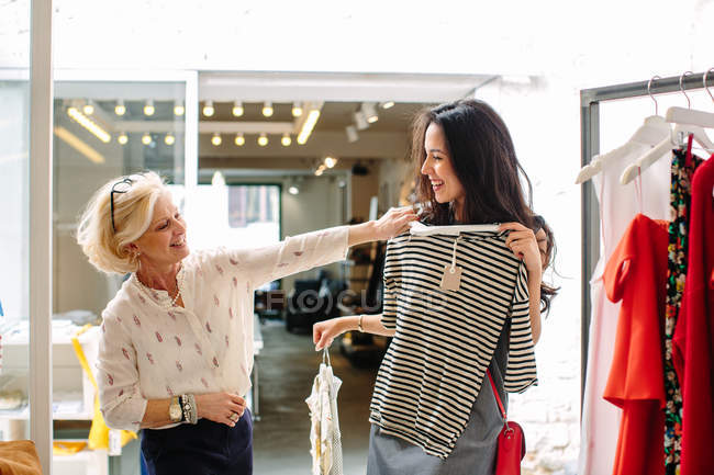 Sales assistant in clothes shop helping customer choose top garment — Stock Photo