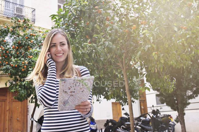 Joven turista femenina con mapa y celular, Valencia, España - foto de stock
