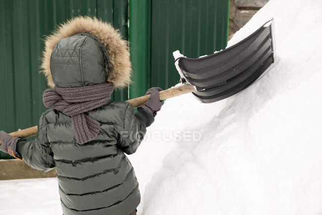 Vista posteriore del bambino in inverno spalando neve — Foto stock